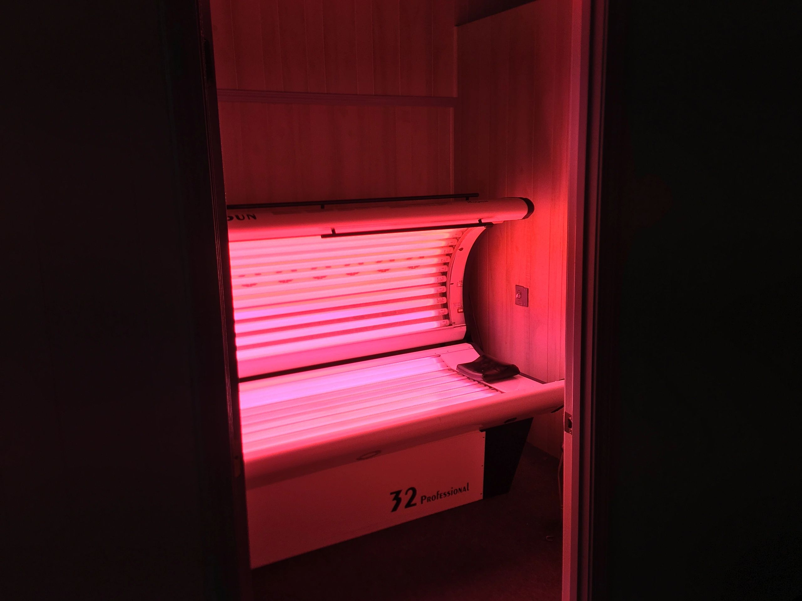 open tanning bed with pink light