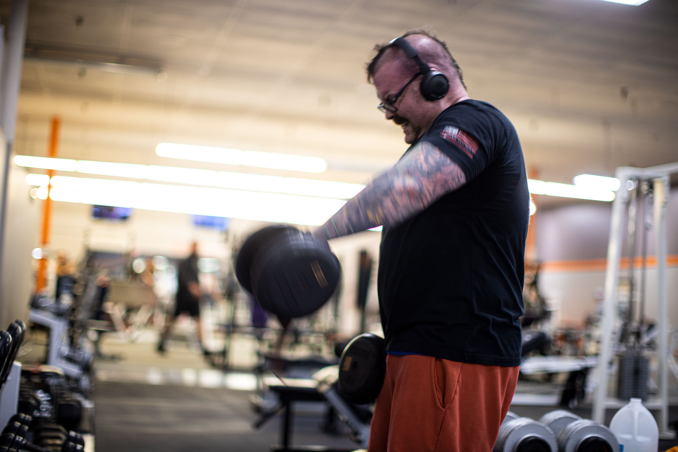 man in black t-shirt and headphones lifting weights
