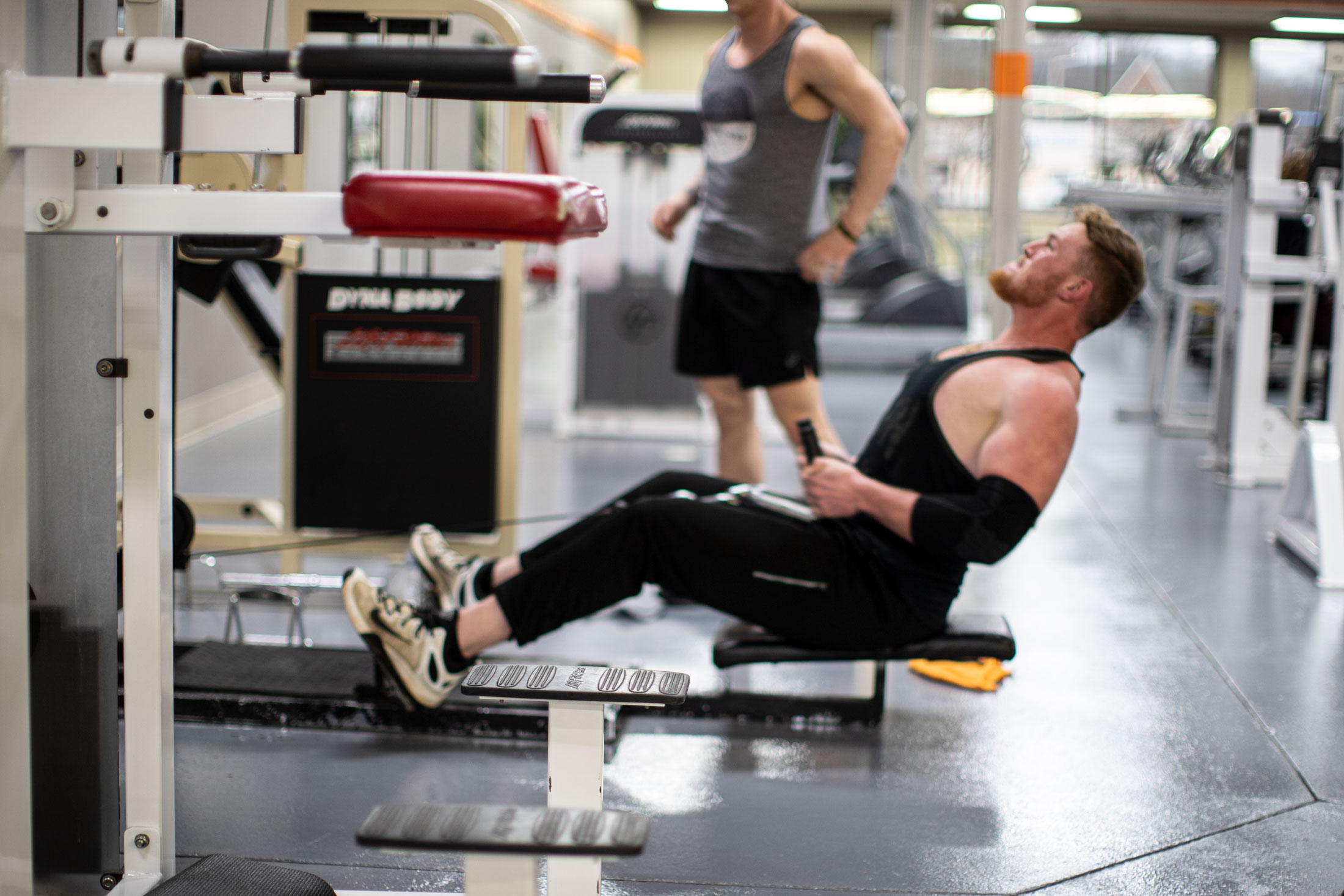 image of man in black tank top using exercise machine