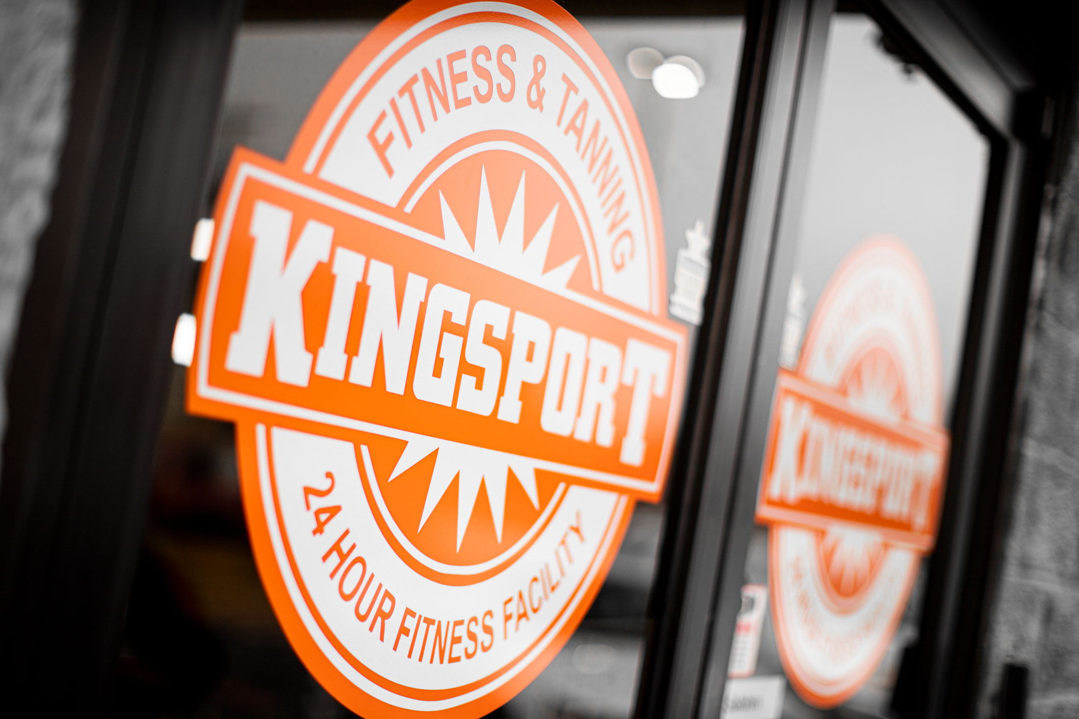 orange and white circular logo with text reading Kingsport Fitness & Tanning 24 Hour Fitness Facility
