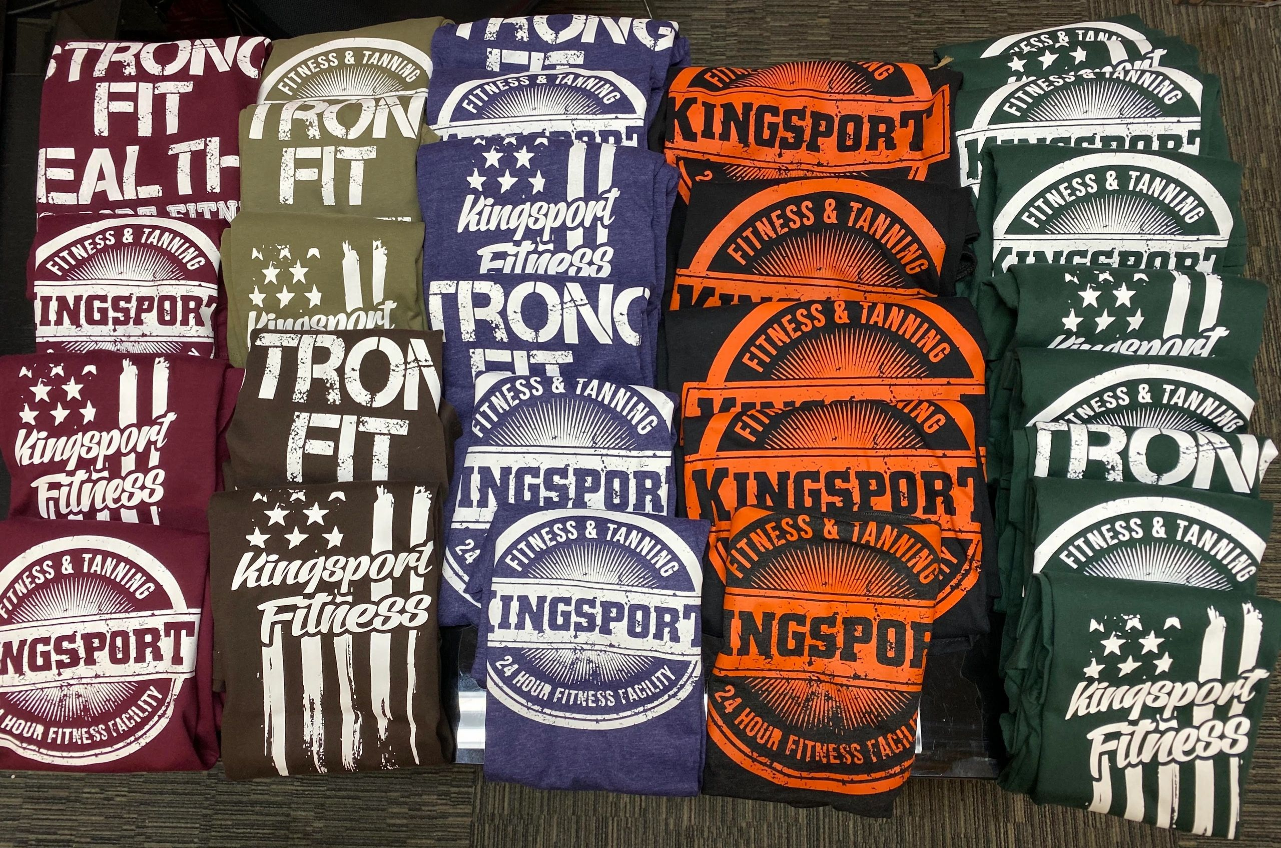 rows of Kingsport Fitness & Tanning t-shirts with various colors and designs